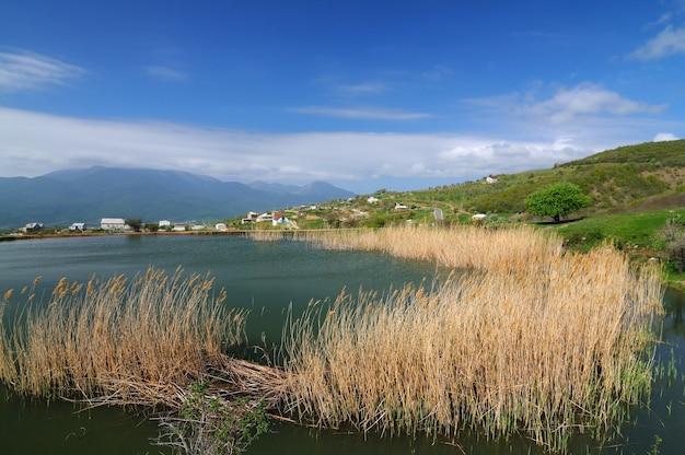 Jezioro z mulistą wodą i rosnącymi trzcinami, błękitnym niebem i małą wioską pośród gór