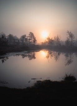 Jezioro z odbiciem słońca z drzewami wokół niego podczas zachodu słońca