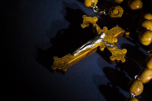 Jezus chrystus katolicki krucyfiks i drewniane koraliki różańca na biblii