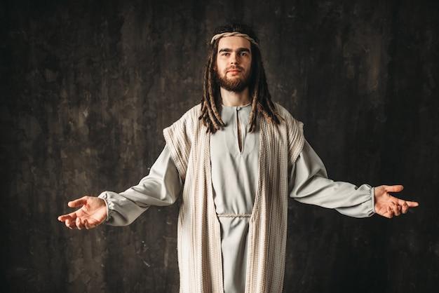 Jezus chrystus modli się z otwartymi ramionami