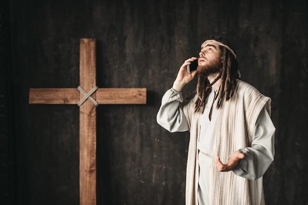 Jezus chrystus rozmawia z bogiem przez telefon komórkowy, krzyż ukrzyżowania na czarno