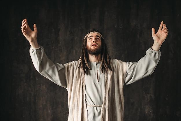 Jezus chrystus w białej szacie modli się emocjonalnie z podniesionymi rękami