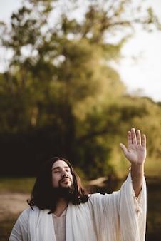 Jezus chrystus wyciąga rękę ku niebu, gdy jego oczy są zamknięte