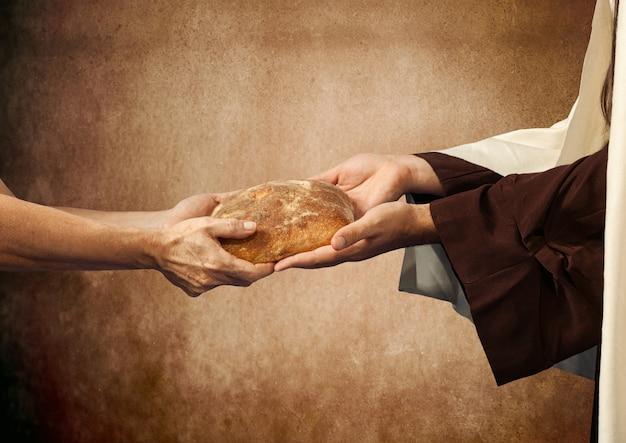Jezus oddaje chleb żebrakowi.