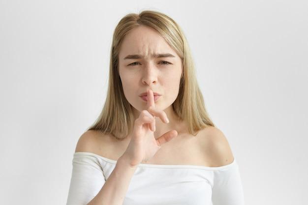 Język ciała. atrakcyjna europejska dziewczyna w stylowej górze trzyma palec wskazujący na ustach i marszczy brwi, prosząc o milczenie. stylowa młoda blondynka robi gest uciszenia, mówiąc: cicho, bądź cicho