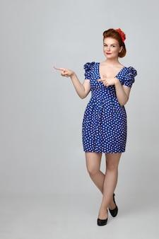 Język ciała. atrakcyjna modna młoda kobieta ubrana w jasny makijaż i strój vintage stojący na białym tle, wskazując palcami, wskazując ścianę copyspace dla tekstu lub reklamy