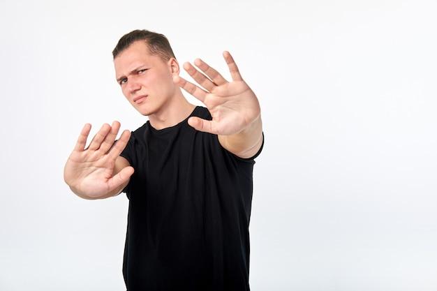 Język ciała. młody nieszczęśliwy człowiek pokazuje gest zaprzeczenia lub zatrzymać.