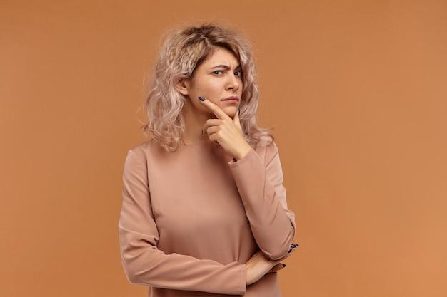Język ciała. portret atrakcyjnej młodej kobiety z kolczykiem w nosie i obszernymi włosami, dotykając twarzy i marszcząc brwi