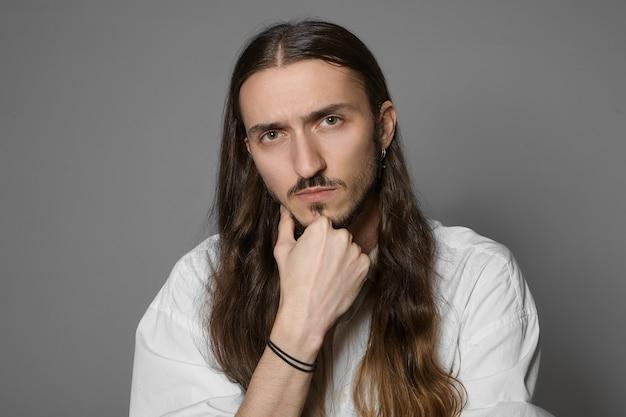 Język ciała. portret przystojnego, nieogolonego młodego europejczyka z wąsami i długą luźną fryzurą dotykającego brody, zastanawiającego się nad jakimś pomysłem, problemem lub projektem, pozowanie na białym tle