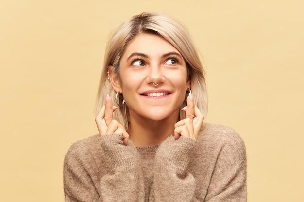 Język ciała. portret uroczej uroczej młodej przesądnej kobiety o blond włosach i kolczyku w nosie trzymających palce na szczęście, pragnącej wygrać na loterii, z oczami pełnymi nadziei i niecierpliwości