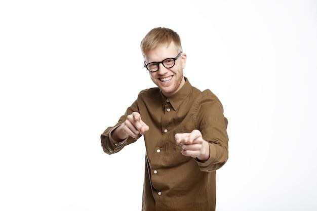 Język ciała. poziome strzał szczęśliwy młody brodaty mężczyzna w modnej koszuli i okularach, śmiejąc się i wskazując na widza