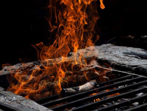 Języki ognia na kratach w ognisku w ciemności