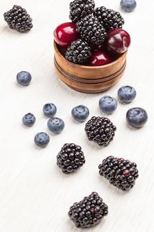 Jeżyna i wiśnia w drewnianym pudełku. czarne jagody i jeżyny na stole. biała powierzchnia, widok z góry.