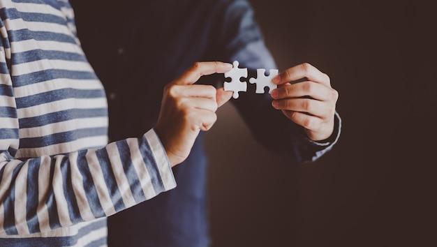 Jigsaw puzzle trzymając się za ręce dwóch osób