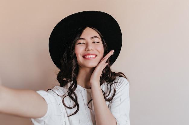 Jocund asian kobieta w kapeluszu, śmiejąc się z kamery. glamorous chinka przy selfie.