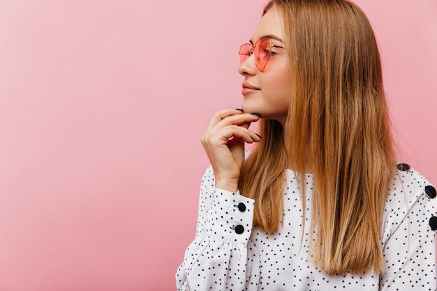 Jocund blondynka w różowych okularach myśli o czymś z uśmiechem. atrakcyjna biała kobieta relaksująca