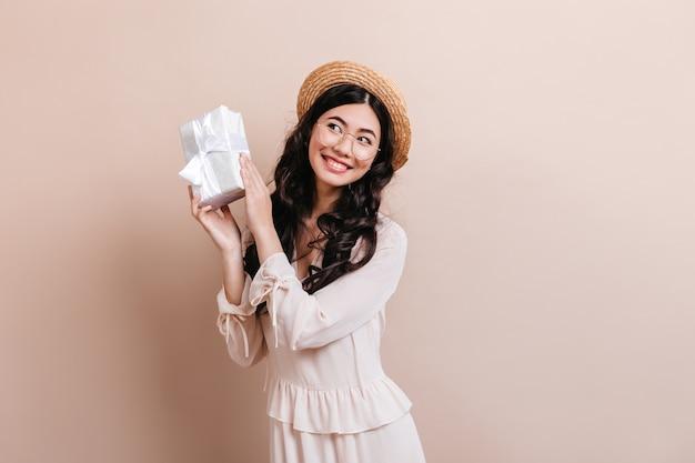 Jocund chinka trzyma prezent urodzinowy. dość kędzierzawy asian kobieta pozuje z prezentem.