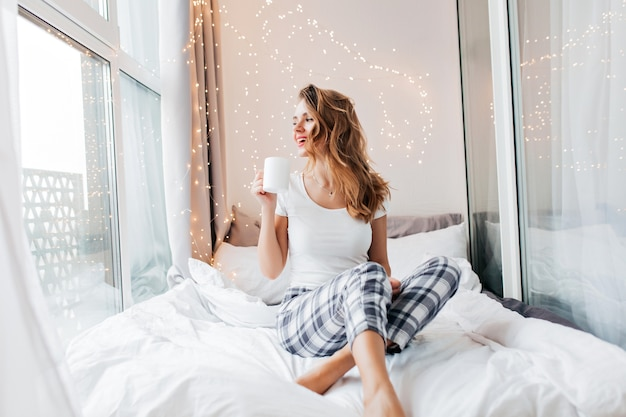 Jocund dziewczyna w bieliźnie nocnej, patrząc w okno. wspaniała modelka w piżamie, ciesząc się kawą wcześnie rano.
