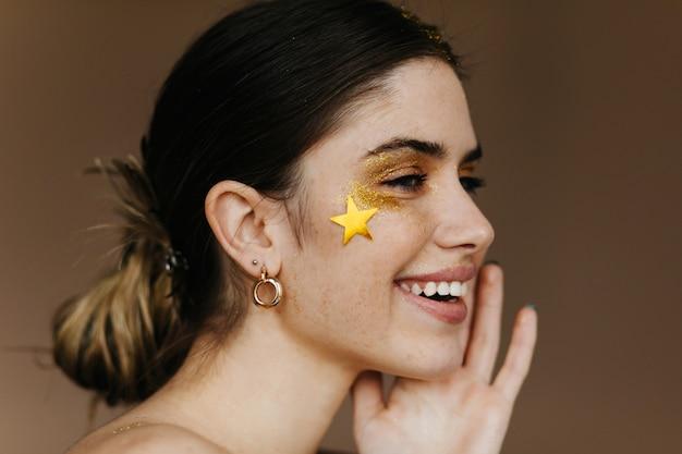Jocund dziewczyna z makijażem partii stojącej na brązowej ścianie. close-up zdjęcie radosnej uśmiechniętej kobiety brunetka.