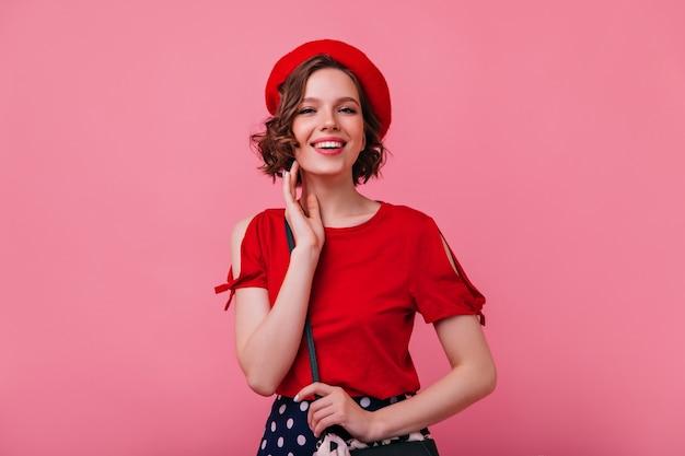 Jocund francuska dziewczyna pozuje z radosną miną. portret eleganckiej stylowej pani w berecie z uśmiechem.