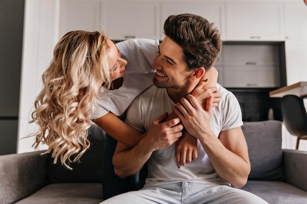 Jocund kręcona kobieta obejmująca męża z miłością. brunetka mężczyzna patrząc na dziewczynę z uśmiechem.