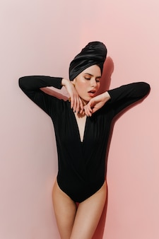 Jocund modelka pozuje w czarnym turbanie i body
