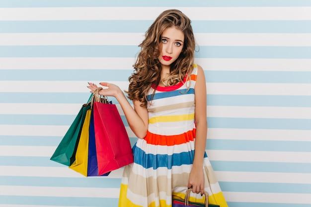 Jocund niebieskooka dziewczyna pozuje po zakupach. kryty zdjęcie zmysłowej kobiety brunetka w jasnej sukience w paski.