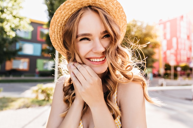 Jocund pani stojąca na ulicy z radosnym uśmiechem. śmiejąc się piękna dziewczyna w słomkowym kapeluszu w słoneczny letni dzień.