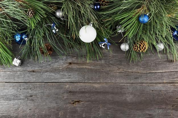 Jodła i biżuteria bożonarodzeniowa na drewnianej powierzchni