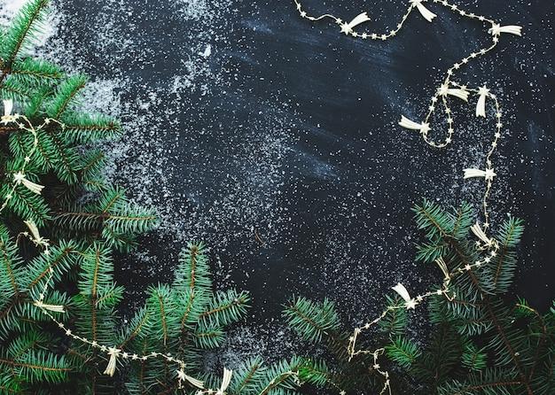 Jodła na ciemnej powierzchni ze śniegiem