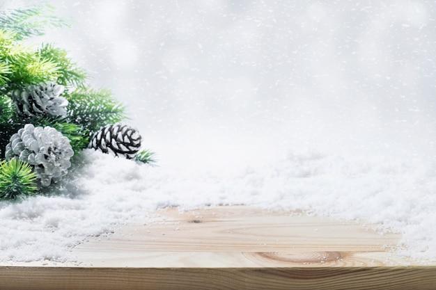 Jodła, szyszki, śnieg na drewnianym stole. ozdoba bożonarodzeniowa