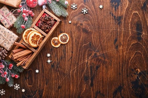 Jodła wystrój czerwony i zielony bombki, w kształcie cynamonu i suche plastry pomarańczy na tle drewna na życzenia świąteczne. widok z góry z miejsca na kopię. kartkę z życzeniami świątecznymi.