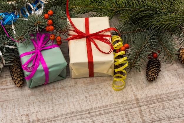 Jodła z pudełkami prezentowymi na drewnianym stole. koncepcja prezentów świątecznych, pocztówka, pozdrowienia