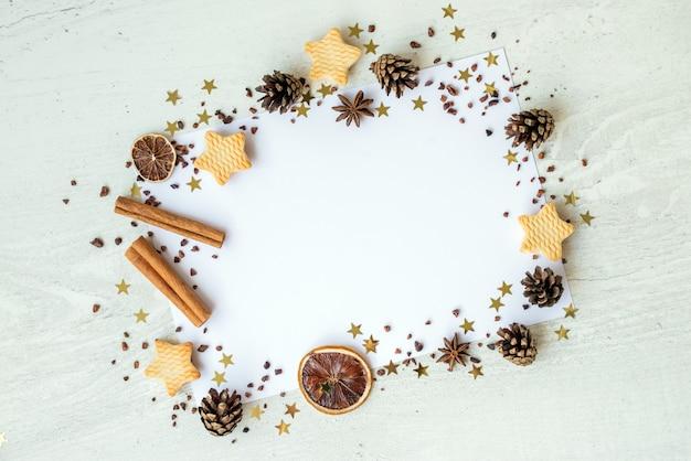 Jodły, ciastka, cynamon i złote wstążki na białym tle. ramka nowa karta nowego roku. koncepcja świąt bożego narodzenia. skopiuj miejsce, leżał płasko