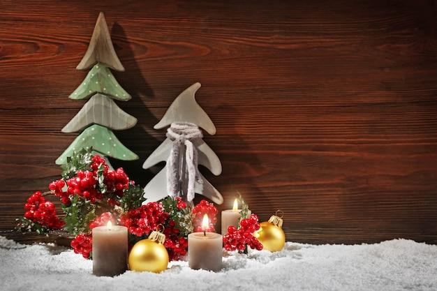 Jodły, świece i kule z brunchem ostrokrzewu w śniegu na drewnianym tle, martwa natura