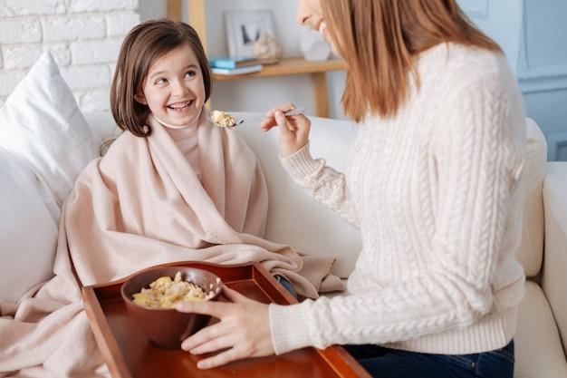 Joful śliczna mała dziewczynka uśmiecha się i je śniadanie z matką, siedząc na kanapie