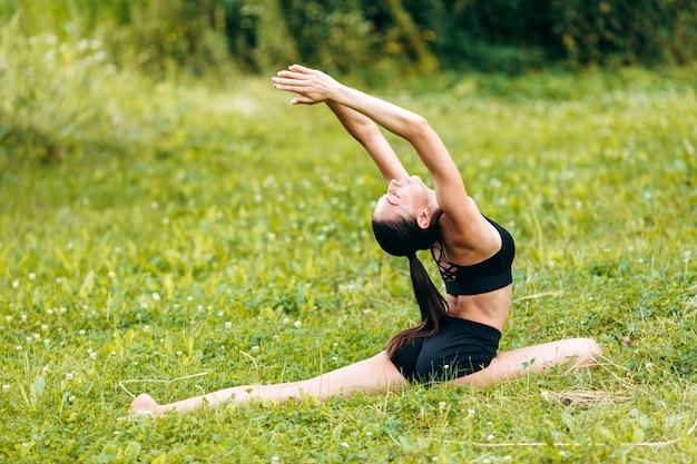 Joga dziewczyna robi asana na trawie w parku plenerowym z rękami up.