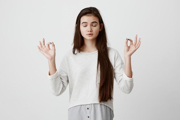 Joga i medytacja. piękna niedbale ubrana brunetka kobieta trzymająca oczy zamknięte podczas medytacji, czująca się zrelaksowana, spokojna i spokojna