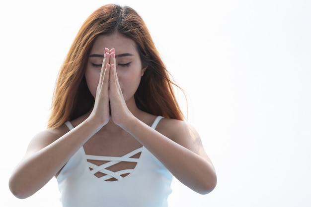 Joga kobieta medytuje z trzymać ręki wpólnie na białym tle.