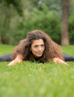 Joga lub fitness w letnim parku. widok z przodu młodej kobiety z długimi kręconymi włosami leżącej na zielonej trawie