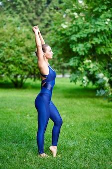 Joga. młoda kobieta ćwiczy joga lub tanczy w naturze przy parkiem. pojęcie zdrowego stylu życia