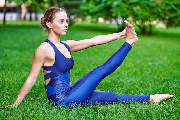Joga. młoda kobieta ćwiczy joga lub taniec w zieleń parku. pojęcie zdrowego stylu życia