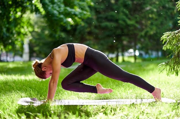 Joga. młoda kobieta ćwiczy joga medytację w naturze przy parkiem. pojęcie zdrowego stylu życia