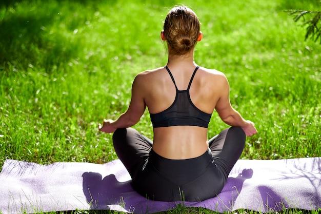 Joga. młoda kobieta ćwiczy joga medytację w naturze przy parkiem. pozycja lotosu. pojęcie zdrowego stylu życia