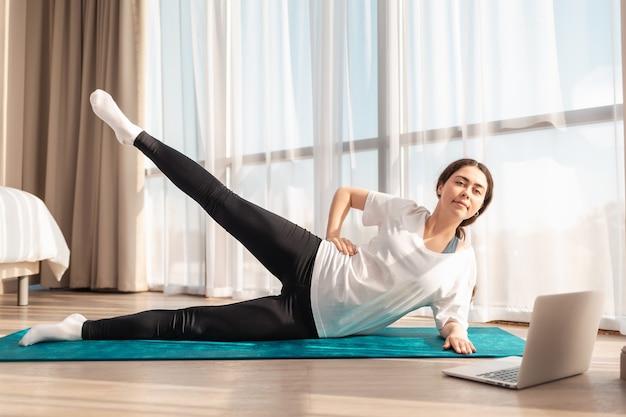 Joga. młoda ładna kobieta trenuje w domu na macie sportowej i wykonuje ćwiczenia nóg. pojęcie treningów domowych.
