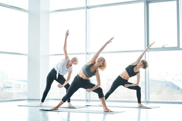 Joga na siłowni. grupa kobiet robi joga obok dużego okna