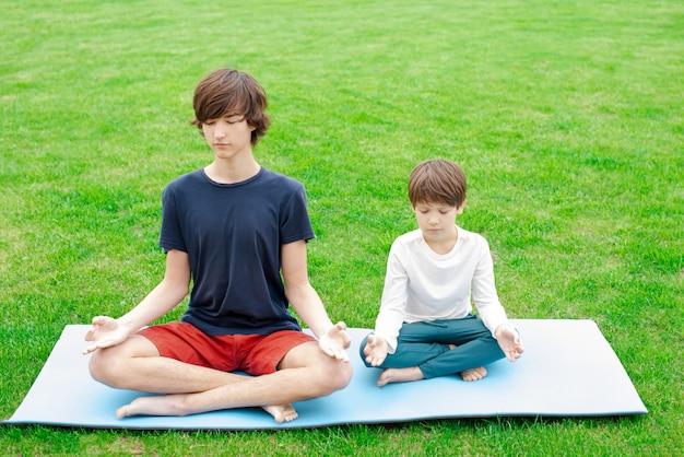 Joga na świeżym powietrzu. dzieci siedzą w pozycji lotosu na zielonej trawie. skopiuj miejsce