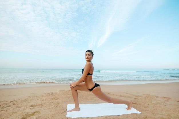 Joga. piękna dziewczyna robi trening jogi. kobieta praktykującafitness w przyrodzie na plaży.