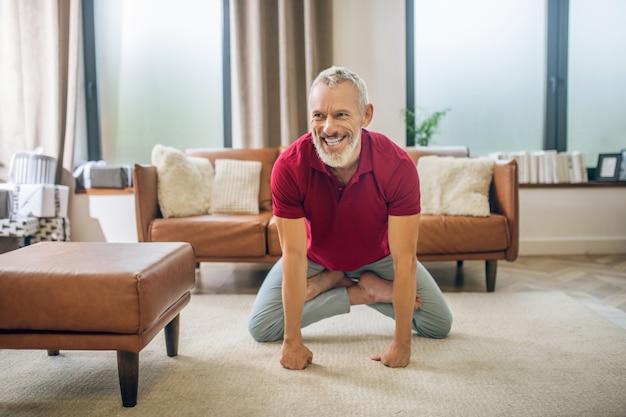 Joga. siwowłosy przystojny mężczyzna ćwiczy jogę i czuje się dobrze