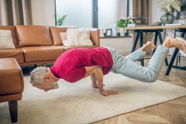 Joga. siwowłosy sprawny mężczyzna robi jogę i wygląda silnie